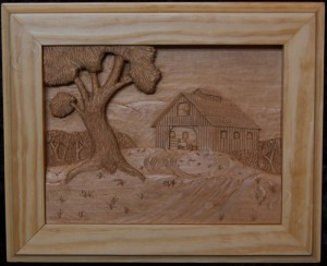 pictorial relief scene of a country landscape with a barn in the background designed and carved by dylan goodson