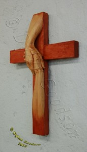 cross with the hand of Jesus grasping another hand carved by Dylan Goodson