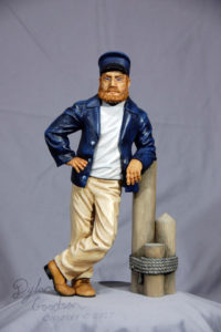 Dylan's woodcarving of a Sea Captain leaning against a dock post
